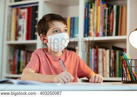Young Student Wearing Protective Mask Working In Isolation On School Assignments. Child Wearing Face