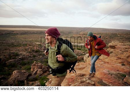 Young Male Hikers With Backpack And Winter Cap Climbing Mountain Trail