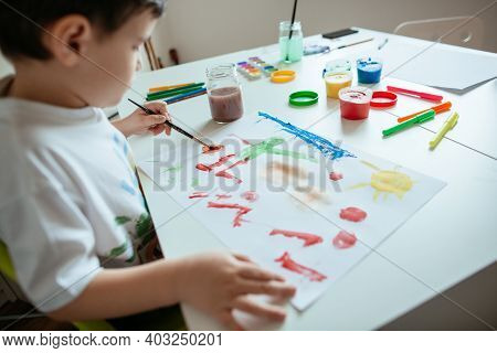 Left Handed Child Painting Picture. Preschooler Boy With Paintbrush And Colorful Paints.