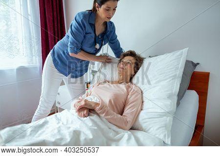 Home Nurse Making Elderly Patient Bed. Female Caregiver Adjusting Pillow For Senior Woman Lying In H