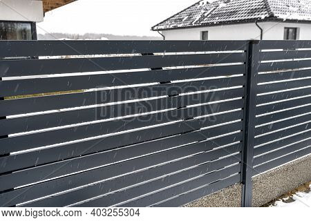 Modern Anthracite Panel Fencing With A Visible Connector Of The Fence Foundations, It Rains In Winte