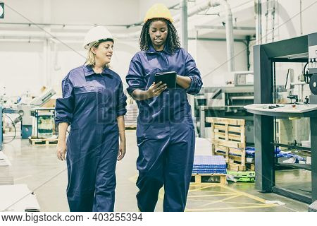Confident Female Plant Workers Talking And Looking At Tablet. Portrait Of Two Multiethnic Colleagues