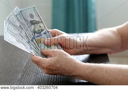 Elderly Woman With Us Dollars In Wrinkled Hands Close Up. Concept Of Pension Payments, Savings At Re