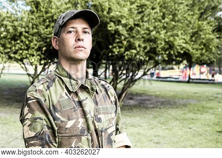 Portrait Of Guard In Park. Serious Man In Military Camouflage Uniform Standing In Park, Looking At C