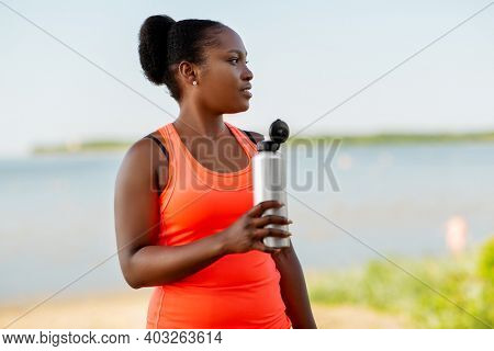 fitness, sport and healthy lifestyle concept - happy smiling young african american woman drinking water from bottle outdoors