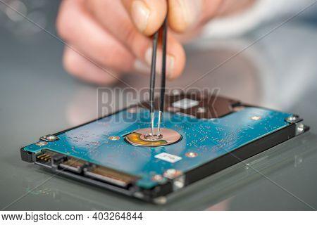 Laptop Hard Drive And Technician Using Tweezers