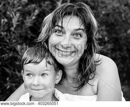 Happy woman and her little son after bathing outdoor. Black and white photo.