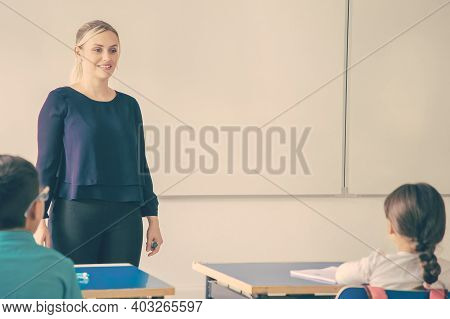 Positive Female Teacher Conducting Class, Standing At Whiteboard, Explaining Task To Primary School