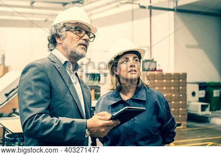 Confident Bearded Supervisor Talking With Female Plant Worker And Holding Tablet. Caucasian Serious