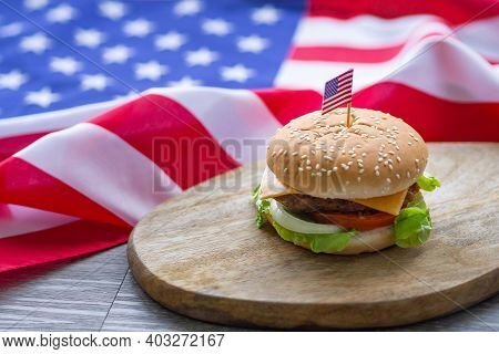 The Close-up Image Of The Homemade Hamburger With Lettuce And Cheese Has An American Flag Pin On The