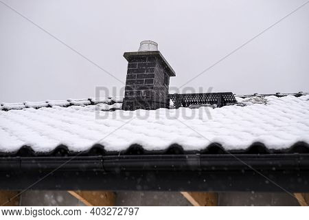 The Roof Of A Detached House Is Covered With Snow Against A Cloudy Sky. Visible System Chimney Cover