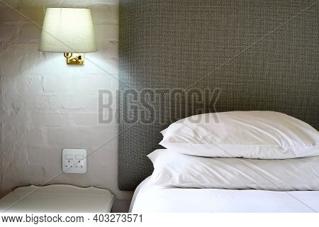 Hotel Room Bed And A Bedside Lamp