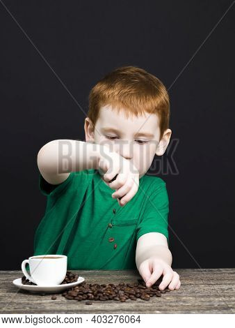 A Red-haired Boy With A Beautiful Face Is Drinking Tea, Coffee Beans Are Lying Next To Him, A Child