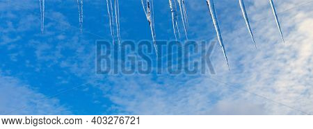 Beautiful Icicles Shine In The Sun Against The Blue Sky. Landscape With Ice Icicles Hanging From The