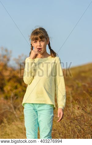 The Girl Nibbles On A Lollipop And Looks At The Frame With A Puzzled Look