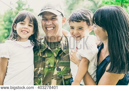 Happy Military Man Posing For Camera With His Family, Holding Kids In Arms, His Wife Hugging All Of