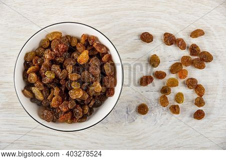 Dried Grape In White Bowl, Few Raisin On Wooden Table. Top View