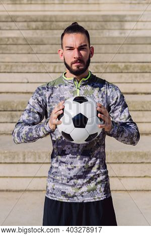 Vertical Portrait Of An Attractive Hipster Sportsman In A Concrete Soccer Court With The Football Ba