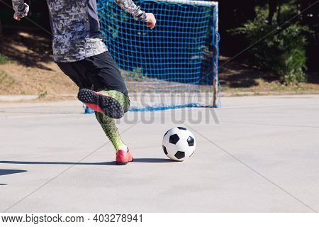 Rear View Of The Legs Of A Football Player Kicking The Soccer Ball Into An Empty Goal In A Concrete