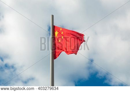 The National Flag Of China People's Republic Of China Waving Against A Cloudy Sky.