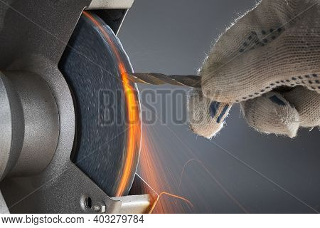 The Hand Wearing A Work Glove Of Man Regrinding The Drill Tool For Sharpen The Drill Tool With Grind