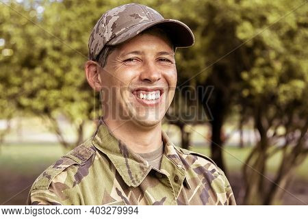 Portrait Of Happy Man In Military Camouflage Uniform Standing In Park, Looking At Camera And Smiling