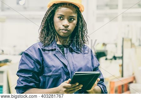 Content Female Plant Worker Standing With Tablet And Looking Away. Portrait Of Pensive African Ameri