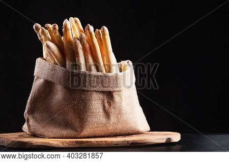 Super Food.healthy Vegetables.white Asparagus In A Cloth Bag On A Kitchen Wooden Board .raw Organic