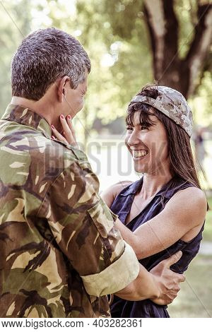 Happy Beautiful Woman Looking At Husband Returning From Army. Cheerful Lady Wearing Soldier Cup, Sta