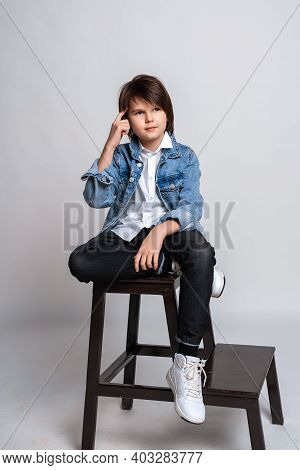 Handsome Fashion Little Boy 11-13 Years Old Sits On A Chair In Studio. Dressed In A White Shirt, Bla