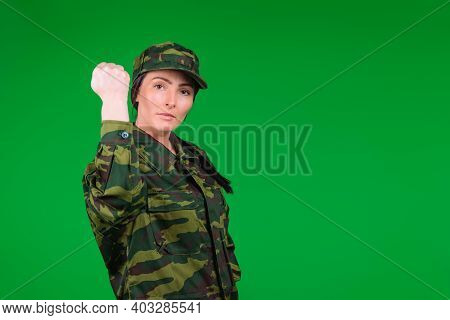 Young Woman In Military Uniform Shows Her Fist To The Camera On A Green Background With Blank Space.