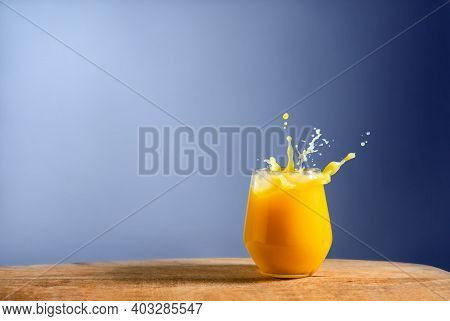 Glass Of Fresh Orange Juice Splash On On Wooden Table And Blue Background. Dynamic Pour Of Fruit Jui