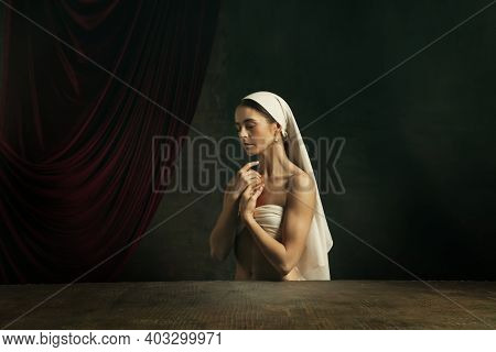 Sadness. Modern Remake Of Classical Artwork - Young Medieval Woman In White Cloth On Dark Studio Bac