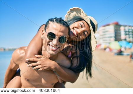 Young latin couple wearing swimwear  smiling happy walking at the beach.