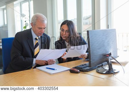 Female Professional Explaining Document Details To Client At Workplace. Serious Business Leader Cons