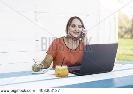 Smiling Woman 40 Years Old Wearing Open Protective Face Mask Using Laptop And Cell Phone During The