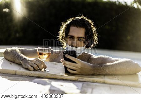 Young Man With Medical Face Mask Having Fun On Poolside Typing With Smartphone And Drinking Rose Win