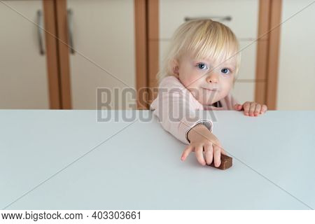Little Blonde Girl Reaches For Chocolate Candy Lying On The Table.
