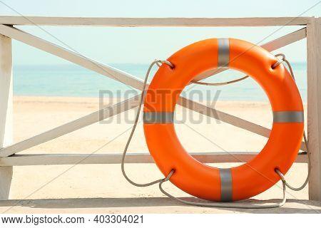 Orange Life Buoy Near Wooden Railing On Beach.  Emergency Rescue Equipment