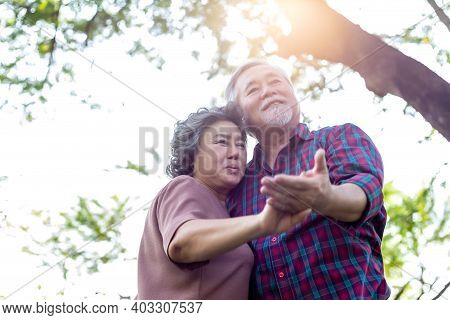 Senior Couple Old Woman Or Wife Dancing With Old Man Or Husband At Park Under Tree In Morning. Grand