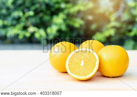 Close-up Of Sliced Orange Fruits On Table With Green Background At Sunrise, Selective Focus On Fresh