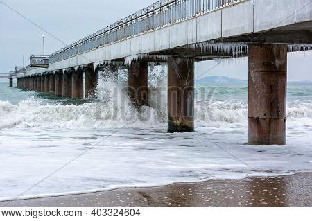 Stormy Winter Black Sea, Burgas Bay, Bulgaria. Winter Landscape. Icicles Hanging On Bridge. Crashing