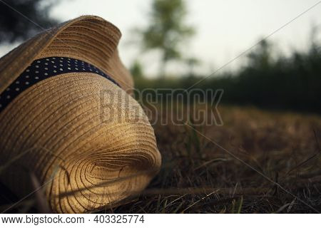 Summer Straw Hat With Blue Ribbon And Dots Lay At Dry End Summer Grass, Beautiful Garden Background