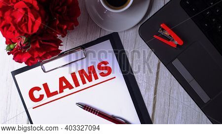 The Word Claims Is Written In Red On A White Notepad Near A Laptop, Coffee, Red Roses And A Pen.