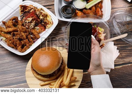 Female Make A Online Order On A Smartphone. Food Container On A Wooden Table. Fast Food Delivery At