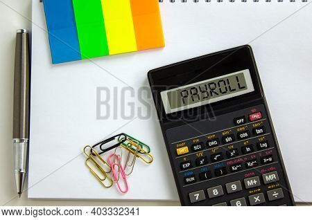 Payroll Symbol. Calculator With The Word Payroll, White Note, Colored Paper, Paper Clips, Pen. Busin