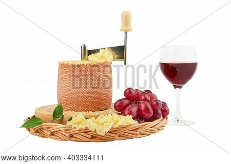 Gourmet Tasty Cheese Tete De Moine, A Glass Of Red Wine And A Bunch Of Grapes Isolated On White Back