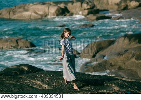 The dancer woman is engaged in choreography on the coast of the ocean.