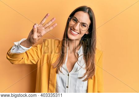 Young beautiful woman wearing business style and glasses showing and pointing up with fingers number three while smiling confident and happy.