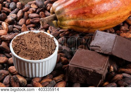 Detail Of Cocoa Fruit With Pieces Of Chocolate And Cocoa Powder On Raw Cocoa Beans.